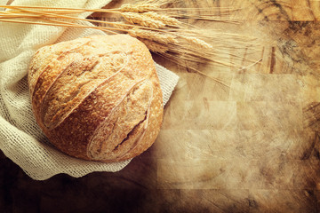 Loaf of bread on rustic cutting board background