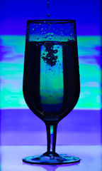 Tinted glass of champagne with splashes of liquid on abstract bl