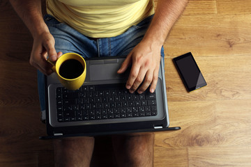 a man sits on a wooden floor with the laptop on my legs and a Cup of coffee in his hands and beside him lays the phone on the floor