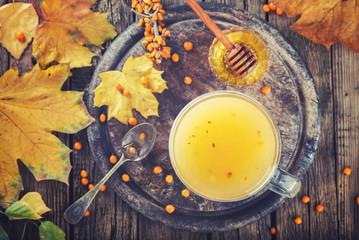Sea buckthorn tea for health.Autumn naturpur on wooden background.