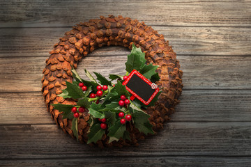 Top view of stylish decorated coniferous wreath on vintage woode