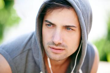 Serious man in sporty hoodie outdoors looking way