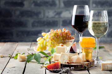 Grape, cheese, figs and honey with a glasses wine.