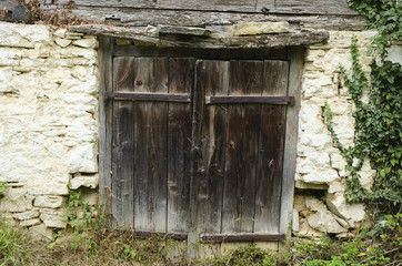 old worn out wooden door with rusty metal hinges