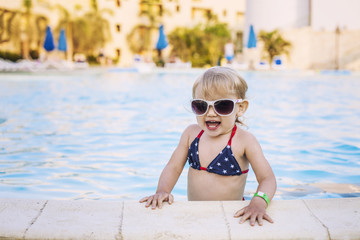 Beautiful baby in the pool happily smiling in sunglasses