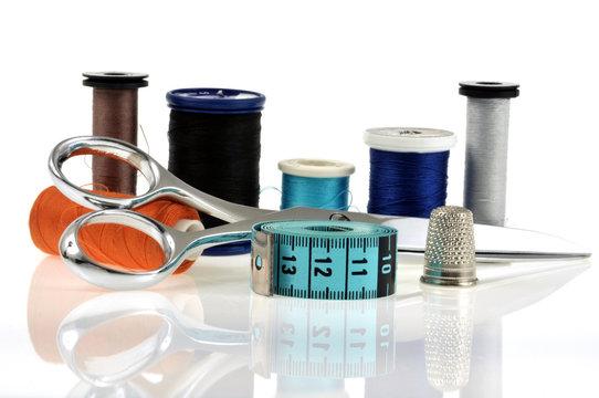 Les bobines de fil, les ciseaux, le mètre de couturière et le dé à coudre
