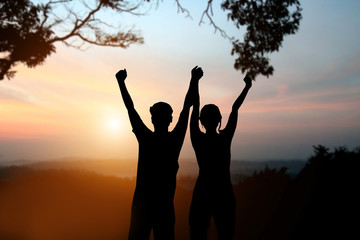 silhouette of man and women show arm up for achievements success
