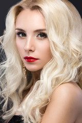 Beautiful blond woman with evening make-up, red lips and curls. Beauty face.