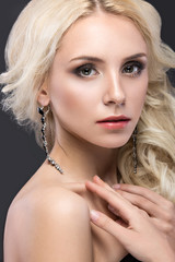 Beautiful blond woman with evening make-up, tender lips and curls. Beauty face.