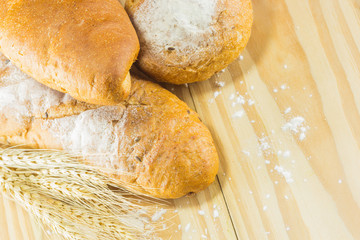 bread and wheat on the wood background, warm toning, selective f