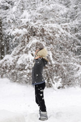 Woman standing in the middle of a snowy woodland welcoming snowf
