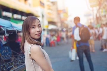 Asia young woman standing on the famous backpacker street Khao San in Bangkok, Thailand.