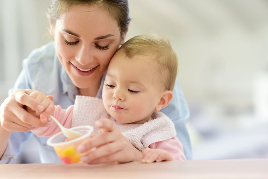 Young mother helping baby girl with eating by herself