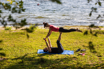 Couple Yoga, man and woman doing yoga exercises outdoor