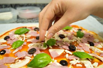 adding mozzarella to the pizza