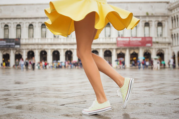 Cheerful young woman wearing sneakers and yellow skirt Wall mural