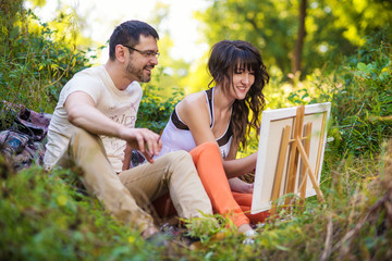Couple Sitting At Outdoor Table Painting Landscape
