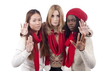 Drei junge Frauen unterschiedlicher Herkunft wehren mit der Hand ab