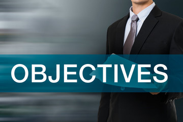 Businessman with OBJECTIVES Word