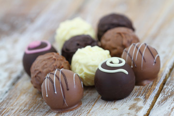 Selection of white, milk and dark chocolates and pralines on rustic wooden surface