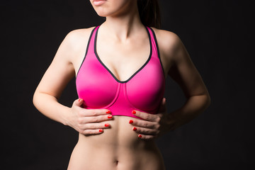 Close up view of sexy sporty woman wearing sports pink bra touching muscular stomach by hands on the black background.