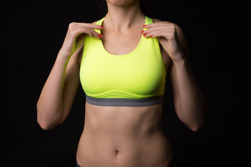 A close up of a sporty woman with a muscular stomach wearing sports touching by hands neon yellow bra on black background.