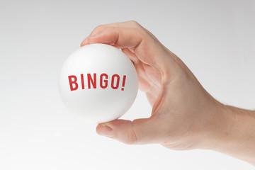 Man's hand holding white styrofoam ball against the white background with Bingo written inside it.