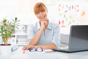 beautiful and confident young woman sitting her desk and looking at the camera