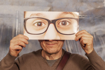 bald man holding a card with a big glasses on it