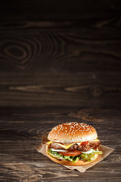 tasty Cheese burger with grilled meat, cheese, tomato, on craft paper on wooden surface. Fast food template.
