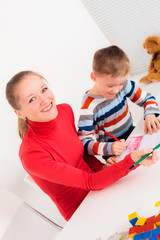 Happy woman and her child drawing together