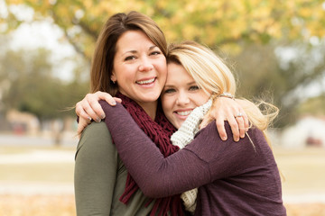 Mother and teenage daughter hugging.