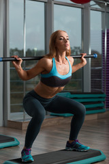 Cute sport woman in fitness room squat with empty bar