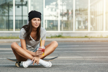 Sexy girl sitting on the skateboard