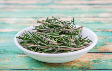 Fresh rosemary herbs over in white bowl over wooden background