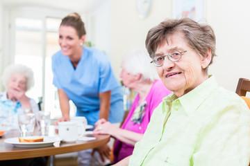 Gruppe Senioren isst in Kantine von Altenheim, eine Pflegerin serviert