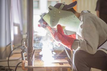 Worker use electric weld steel