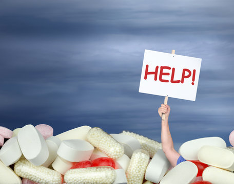 A huge pile of various pills with a man's hand coming out of the pills holding a sign that says HELP! representing drug abuse, addiction, chronic pain, medication confusion, and medical guidance help.