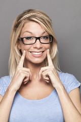 serious 20s blonde girl expressing joy with fake smile