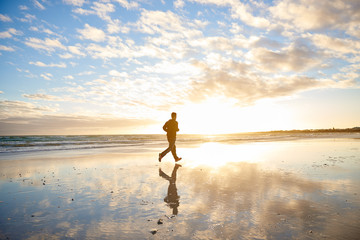 Man running on the beach with clouds and sun flare