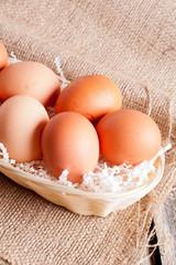 Eggs in Wicker basket on a wooden background