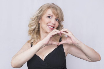 Older blonde woman showing a heart shape