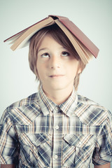 schoolboy with book over head