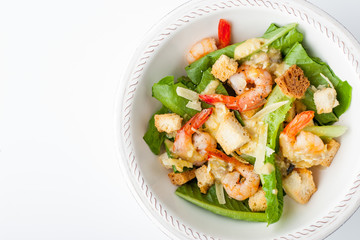 Caesar salad with shrimps on the white background top view