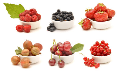 Collection of berries in white bowls: raspberry, blackberry, strawberry, gooseberry, cherry, redcurrant