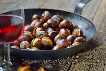 Pfanne mit frisch gerösteten Maronen. mit einem Glas Vernatsch zum Törggelen in Südtirol serviert