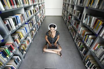 Giovane ragazza ascolta musica con le cuffie in biblioteca