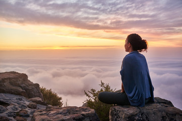 Woman on a mountain top looking at morning clouds Fotomurales