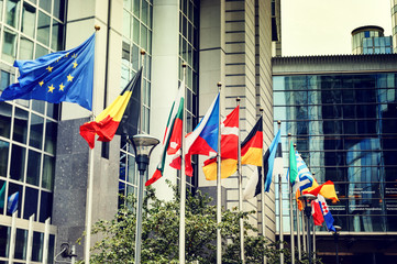 Waving flags in front of European Parliament building in Brussel