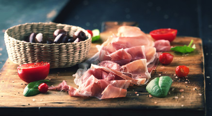 Prosciutto with bread on a wooden board with olives